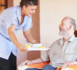 caregiver giving meal to senior man